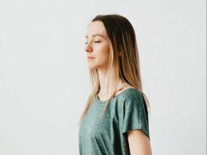 Calm woman sitting in hero pose on yoga mat